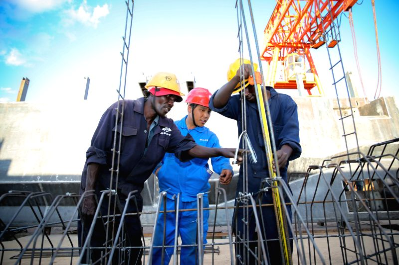Wang Xinjiang (C), a Chinese engineer, works with Kenyan workers at the T-beam factory on section six of Kenya's Standard Gauge Railway project, near Makueni, Kenya, ...