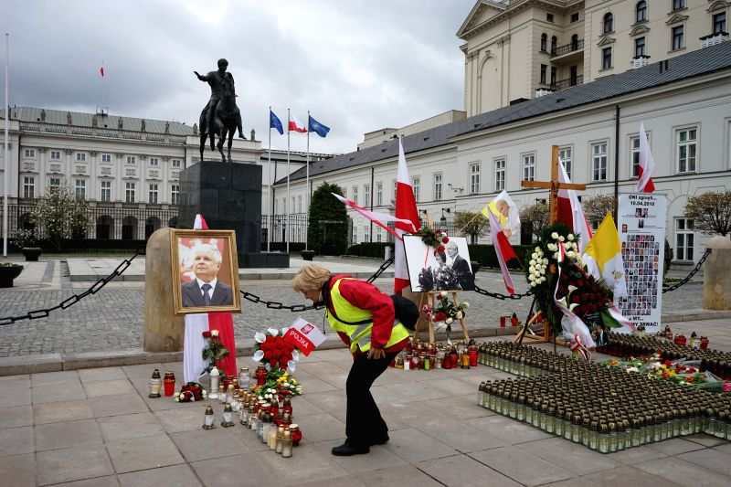 A woman mourns for victims of the plane crash in front of the presidential office in Warsaw, Poland, April 10, 2014. Poland witnessed the 4th anniversary of the ...