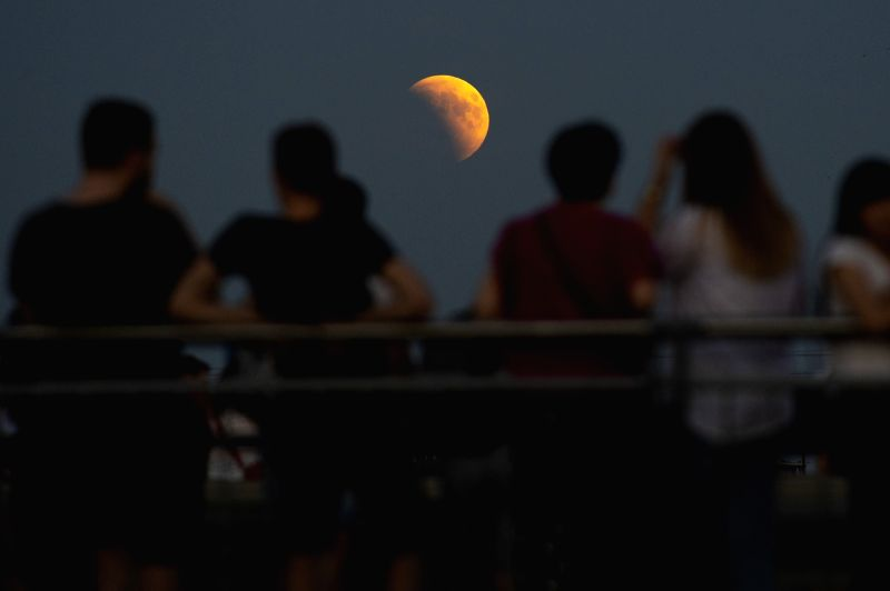 WARSAW, July 28, 2018 - People gather near the Copernicus Science Center to watch the lunar eclipse in Warsaw, Poland on July 27, 2018.