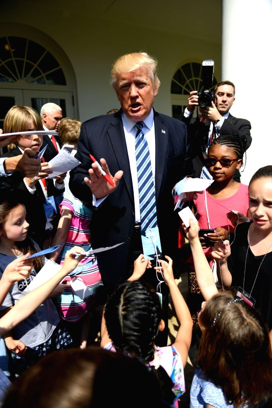 "WASHINGTON, April 27, 2017 - U.S. President Donald Trump (C) signs autographs for children of White House staffers and reporters during ""Take Our Daughters and Sons to Work Day"" at the ..."