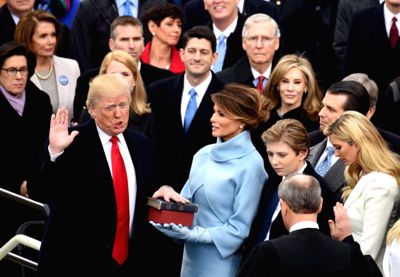 WASHINGTON, April 29, 2017 - File photo taken on Jan. 20, 2017 shows U.S. President Donald Trump (L) taking the oath of office during the presidential inauguration ceremony at the U.S. Capitol in ...