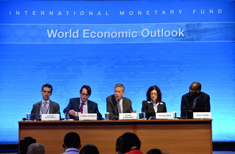 Olivier Blanchard (C), chief economist of the International Monetary Fund (IMF), speaks during a press briefing on the World Economic Outlook at IMF ...
