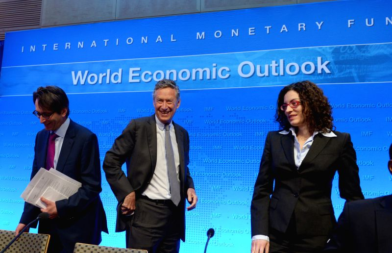 Olivier Blanchard (C), chief economist of the International Monetary Fund (IMF), attends a press briefing on the World Economic Outlook at IMF Headquarters ...