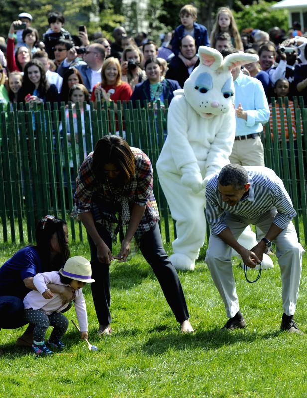 U.S. President Barack Obama (R) participates in an egg roll race during the White House Easter Egg Roll on the South Lawn of the White House in Washington .