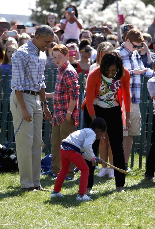 U.S. President Barack Obama (L) participates in an egg roll race during the White House Easter Egg Roll on the South Lawn of the White House in Washington ...