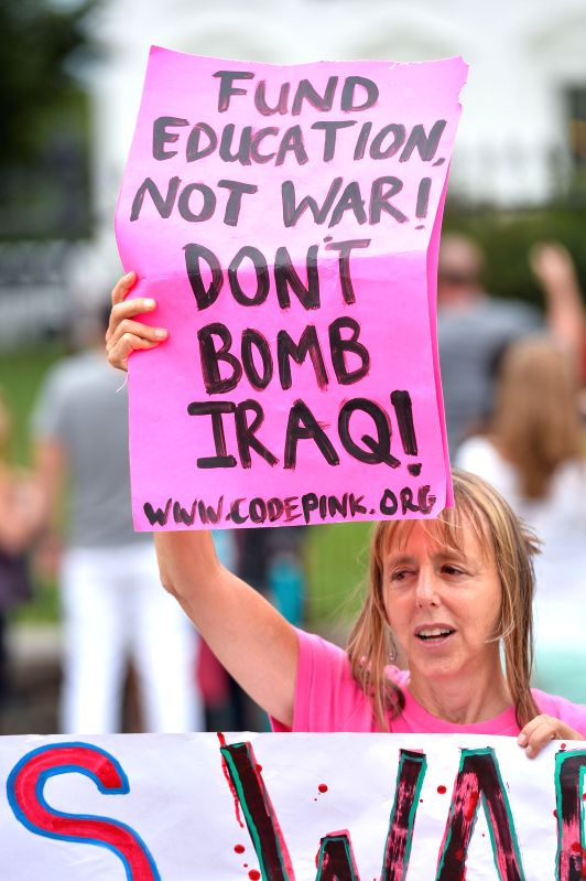 A woman attends a rally to protest the U.S. airstrikes in Iraq outside the White House in Washington D.C., capital of the United States, Aug. 11, ...