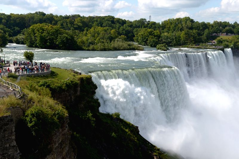 Tourists enjoy themselves at the Niagara Falls near the border between the United States and Canada on Aug. 17, 2014.