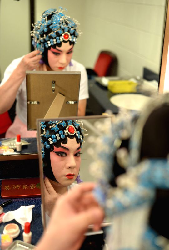 "Peking Opera actor Hu Wenge prepares to perform ""Lady Mu Guiying Takes Command"" at the back stage of the Kennedy Center of the Performing Arts in ."