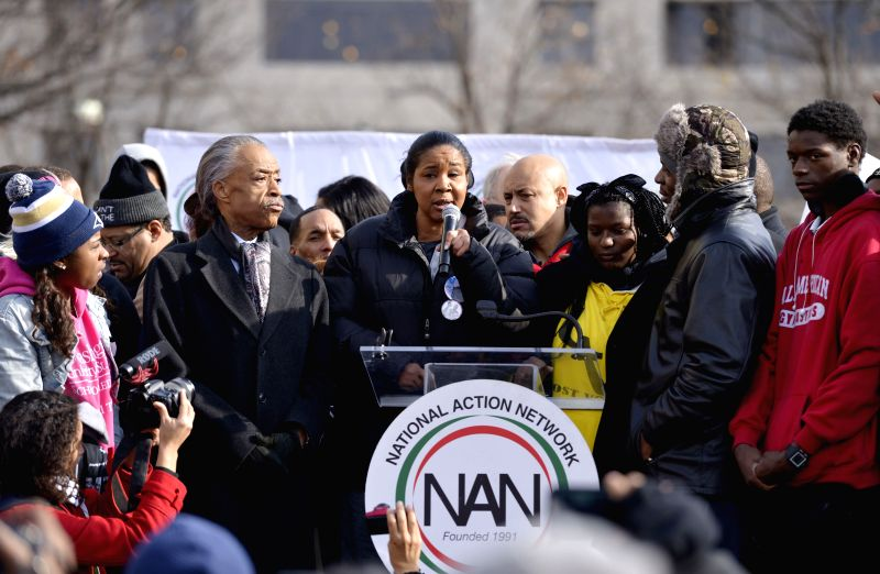 Wife of Eric Garner (C), who was chokeholded to death, speaks during a demonstration at the Freedom Plaza near the White House protesting against racism and