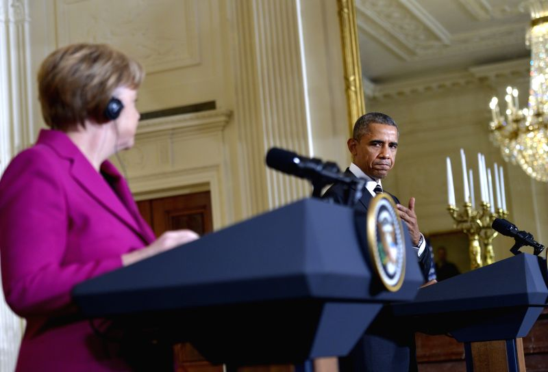 U.S. President Barack Obama (R) speaks as German Chancellor Angela Merkel listens during their joint news conference in the East Room of the White House in ..
