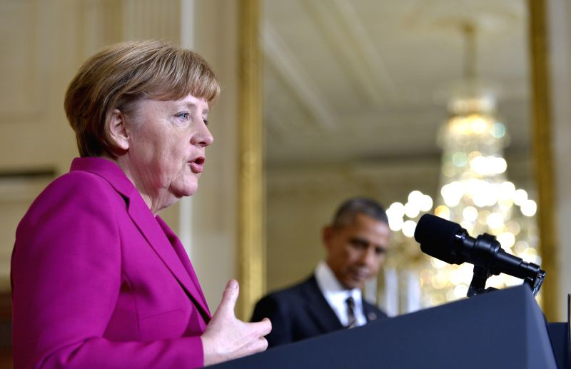 U.S. President Barack Obama (R) listens as German Chancellor Angela Merkel speaks during their joint news conference in the East Room of the White House in ..