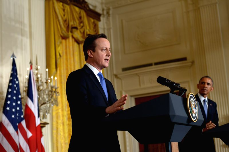 U.S. President Barack Obama (R) listens as British Prime Minister David Cameron speaks during their joint news conference in the East Room of the White ... - David Cameron