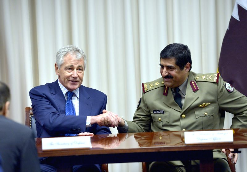 U.S. Defense Secretary Chuck Hagel (L) and Qatar's Minister of State for Defense Affairs Hamad bin Ali al-Attiyah shake hands after signing documents at the