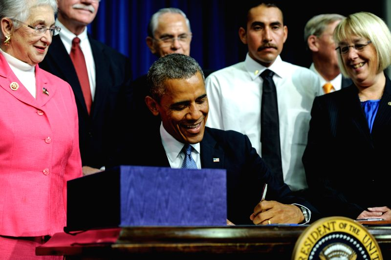 U.S. President Barack Obama (C) signs the Workforce Innovation and Opportunity Act at White House in Washington D.C., capital of the United States, July 22, ..