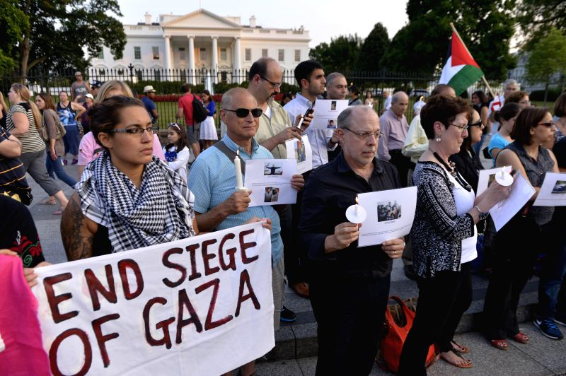 People attend a candlelight vigil for Palestinians who lost their lives in Israel's current military operations in Gaza in front of the White House in ...