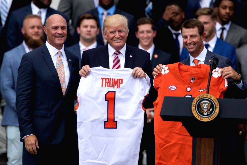 WASHINGTON D.C., June 13, 2017 - U.S. President Donald Trump poses with football jerseys during a ceremony honoring the 2016 NCAA Football National Champions Clemson University Tigers at the White ...