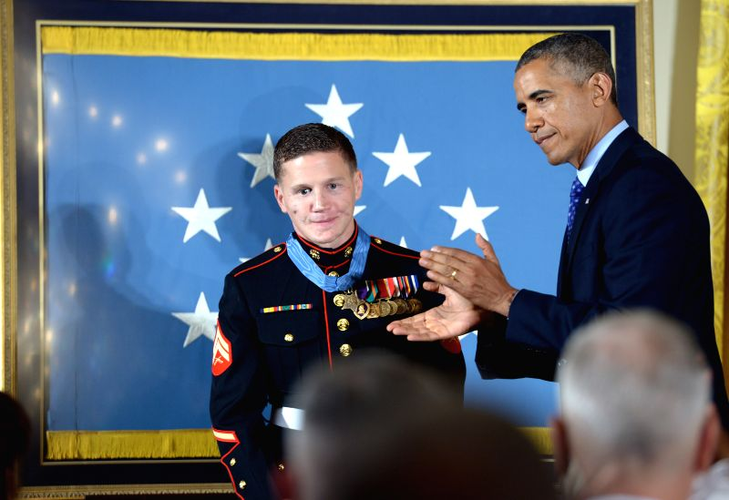 "U.S. President Barack Obama (R) applauds at a ceremony after awarding William ""Kyle"" Carpenter (L) with the Medal of Honor in the East Room of the"