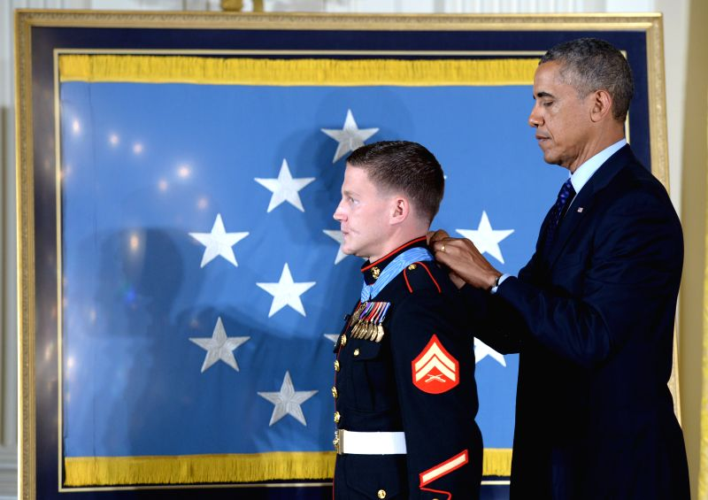 "William ""Kyle"" Carpenter (L) receives the Medal of Honor from U.S. President Barack Obama during a ceremony in the East Room of the White House in"