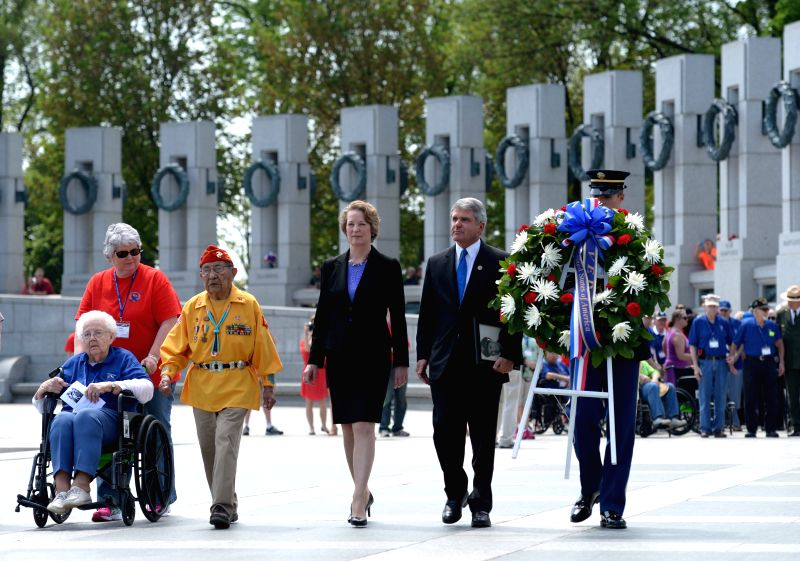 Photo: Susan Eisenhower (C), granddaughter of late President Dwight D. Eisenhower, and World War II veterans walk to place a wreath during a ceremony marking .