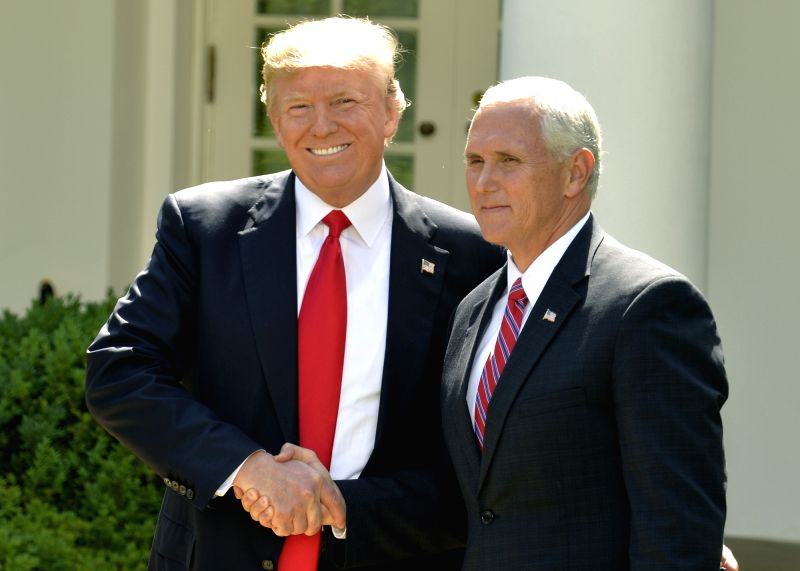 WASHINGTON, June 1, 2017 - U.S. President Donald Trump (L) shakes hands with U.S. Vice President Mike Pence before delivering a speech at the White House in Washington D.C., capital of the United ...