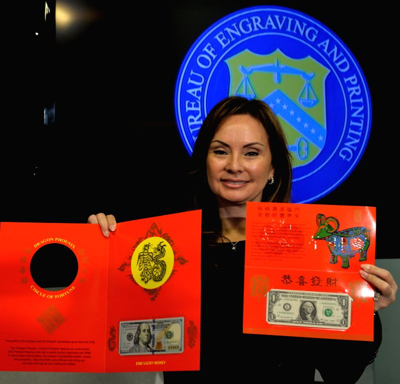 "U.S. Treasurer Rosie Rios displays the ""$1 Year of the Goat 2015 and $100 Dragon-Phoenix Circle of Fortune"" lucky money notes during a press conference in Washington D.C., ..."