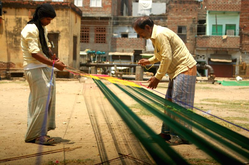 Weavers weave sarees even on International Workers' Day which is celebrated worldwide on 1st May to commemorate the historic struggle of workers for their rights, in Varanasi on May 1, 2014.