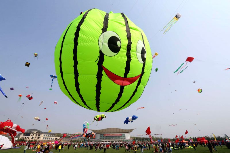 Participants fly kites during a kite fair held in Weifang, east China's Shandong Province, April 18, 2015. Kites-flying fans from China and abroad took part in the ...