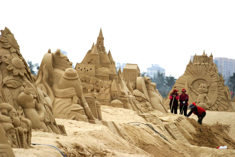 Artists create sand sculptures on a seashore in Weihai, east China's Shandong Province, April 26, 2014.