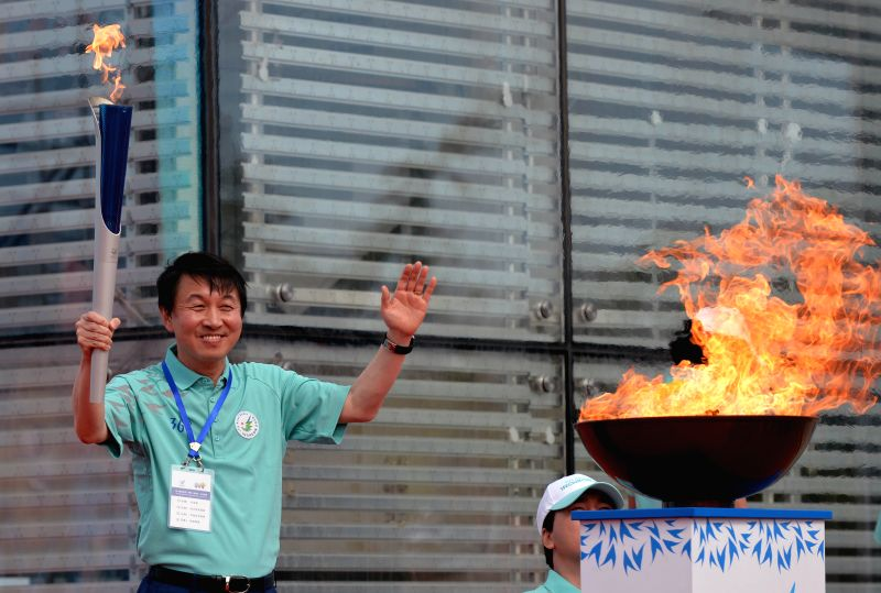 The official of Inchon 2014 Asian Games Kwon Kyungsang gestrues after lighting the caldron during the torch relay of Inchon 2014 Asian Games in Weihai, Shandong ...