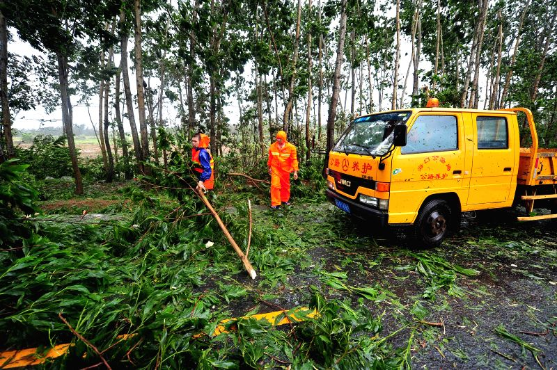 Municipal workers clear tree branches off the road in Wenchang, south China's island of Hainan Province, July 18, 2014. A man was killed when super typhoon ...
