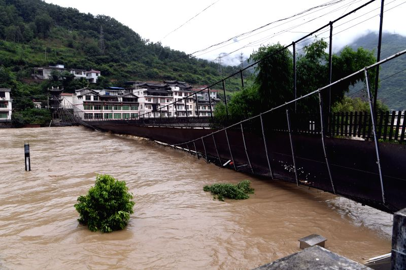 WENXIAN, July 12, 2018 - A suspension bridge is damaged by flood in Bikou Town of Wenxian County, northwest China's Gansu Province, July 12, 2018. Water levels in the Yangtze River and the Yellow ...