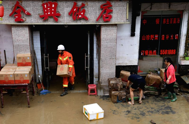 WENXIAN, July 13, 2018 - A firefighter transfers items from a flooded restaurant in Bikou Township of Wenxian County, northwest China's Gansu Province, July 13, 2018. China's disaster relief ...