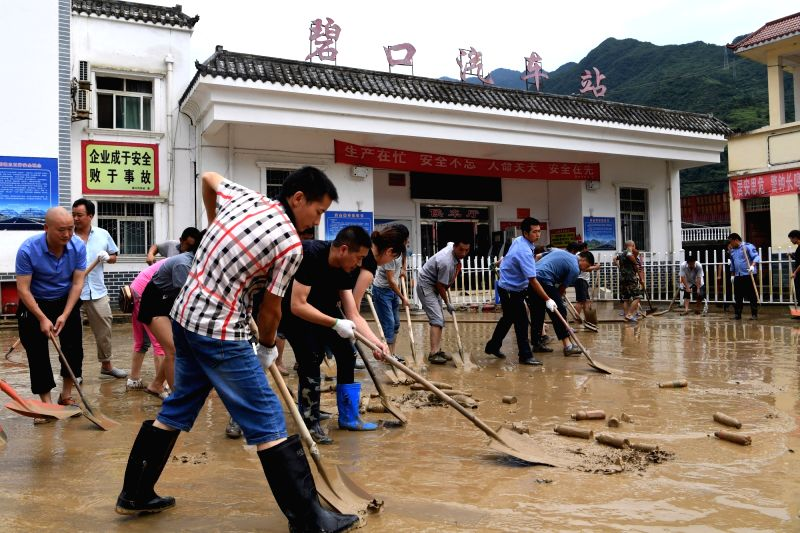 WENXIAN, July 13, 2018 - People clear up the mud on road in flood-hit Bikou Township of Wenxian County, northwest China's Gansu Province, July 13, 2018. China's disaster relief authorities launched a ...