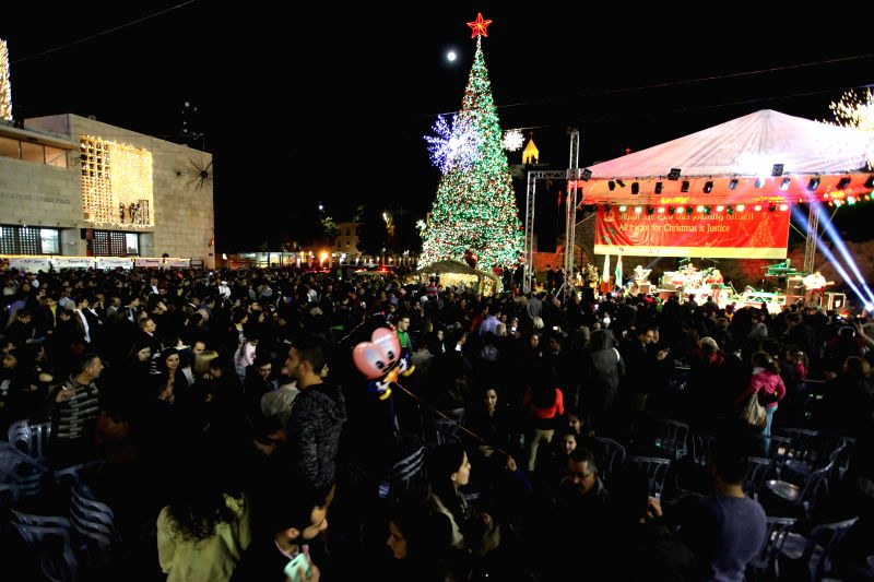 West Bank city (Bethlehem ): People participate in the lighting ceremony of the Main Christmas tree at the Manger Square, outside the Church of the Nativity in West Bank city of Bethlehem on Dec. 6, .