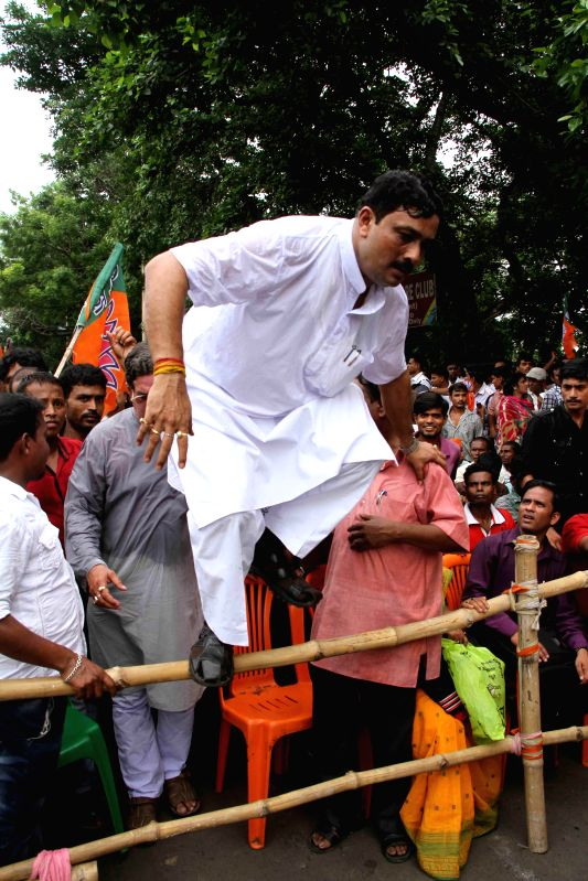 West Bengal BJP chief Rahul Sinha jumps a barricade during a  protest rally against West Bengal Government in Kolkata on June 23, 2014. - Rahul Sinha