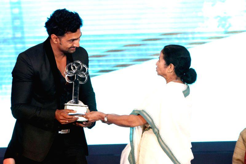 West Bengal Chief Minister Mamata Banerjee presents a award to tollywood actor and TMC MP Dev during `Mahanayak Sanman 2014` on 34th death anniversary of actor Uttam Kumar in Kolkata on July 24, ... - Mamata Banerjee