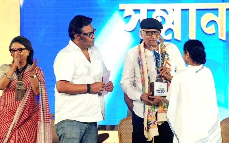West Bengal Chief Minister Mamata Banerjee confers Mahanayak Samman on actor Paran Bandopadhyay during an award ceremony, in Kolkata on July 24, 2018. - Mamata Banerjee