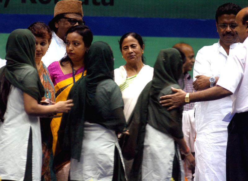 West Bengal Chief minister Mamata Banerjee and West Bengal Urban Development Minister Firhad Hakim with children during a programme in Kolkata on June 19, 2014.
