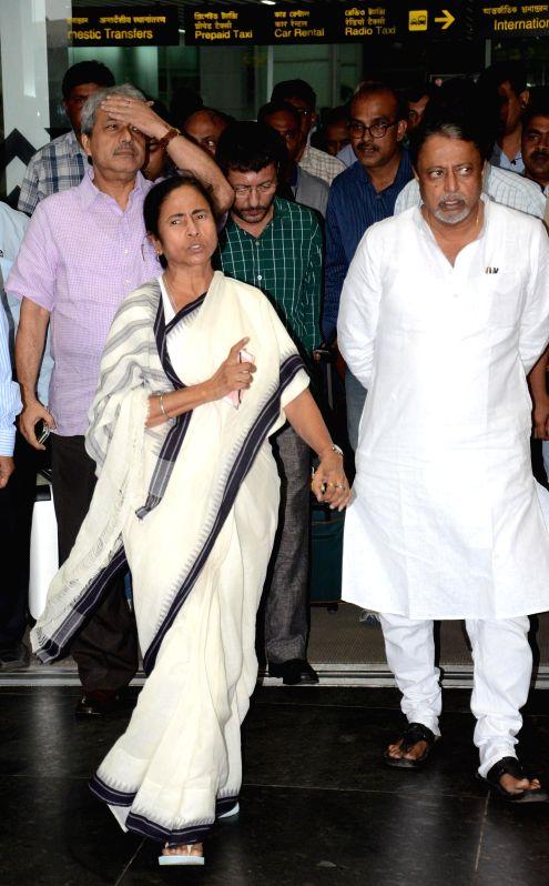 West Bengal Chief Minister Mamata Banerjee and Trinamool Congress General Secretary Mukul Roy arrive at Netaji Subhash Chandra Bose Airport in Kolkata on July 19, 2014. Banerjee was on a North Bengal - Mamata Banerjee
