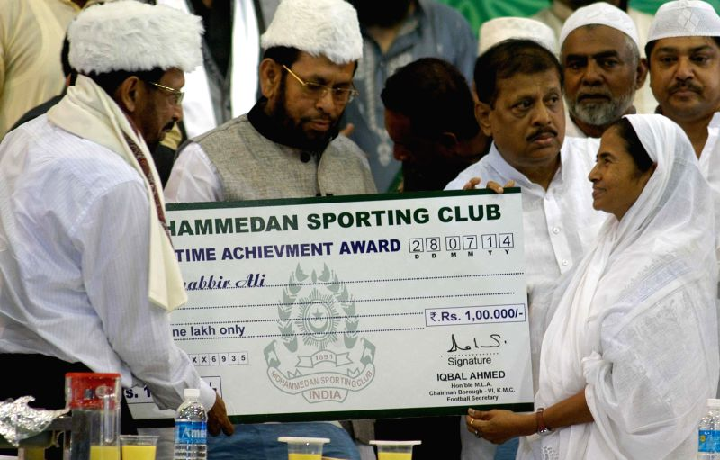 West Bengal Chief Minister Mamata Banerjee hands over Life Time Achievement to former footballer Sabbir Ali during an iftaar party organised by Mohammedan Sporting Club in Kolkata on July 28, 2014. - Mamata Banerjee