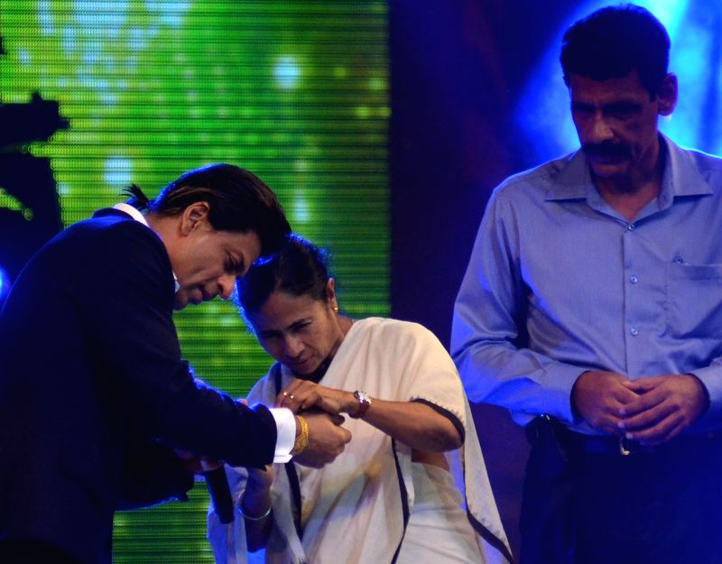 West Bengal Chief Minister Mamata Banerjee tying rakhi on the wrist of Actor Shahrukh Khan during a program in Kolkata on Aug 9, 2014. - Mamata Banerjee