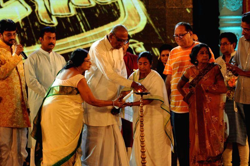West Bengal Chief Minister Mamata Banerjee with veteran actress Madhobi Mukherjee, Sabitri Chatterjee, vocalist Dwijen Bandopadhay lighting the lamp during Tele Academy Award 2015-16 in ... - Mamata Banerjee, Madhobi Mukherjee and Sabitri Chatterjee