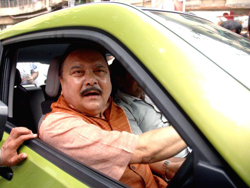 West Bengal Transport Minister Madan Mitra drives Mahindra Reva E20 - an electric car in Kolkata on June 24, 2014.