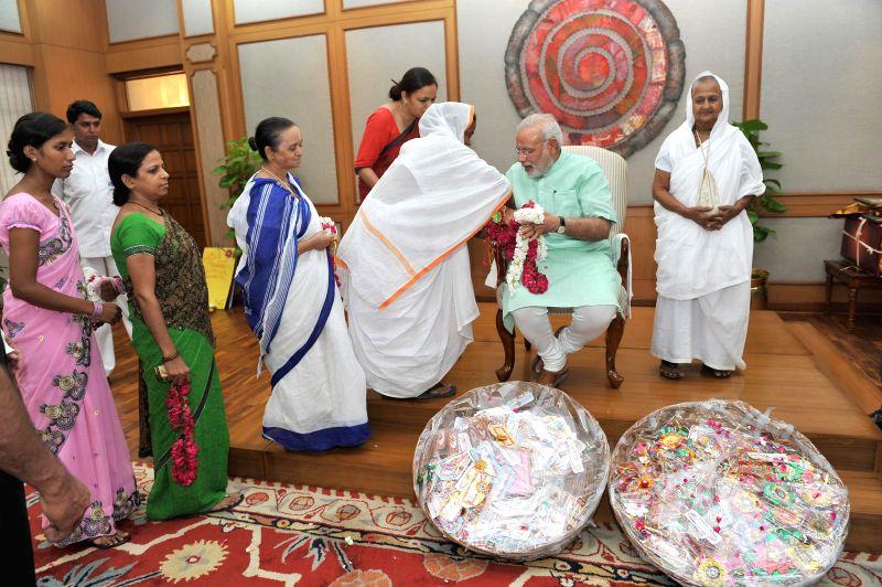 Widows from Vrindavan and Varanasi tie  'rakhi' to Prime Minister Narendra Modi on the occasion of 'Raksha Bandhan', in New Delhi on August 10, 2014. - Narendra Modi