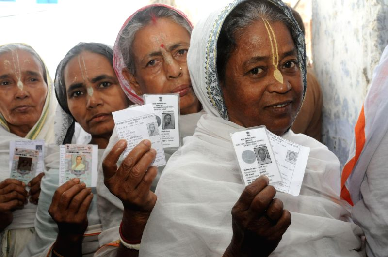 Widows of Vrindavan show their voter's identity card as they queue-up to cast their vote at a polling booth in Vrindavan of Uttar Pradesh's Mathura district on April 24, 2014.