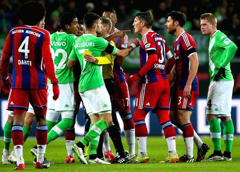 Luiz Gustavo (2nd L) of Wolfsburg points to Bastian Schweinsteiger (3rd R) of Bayern Munich during their German first division Bundesliga football match in ...