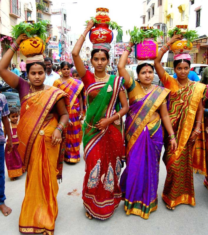 Woman dressed in traditional attire participate in a Bonalu procession in Hyderabad on July 20, 2014.