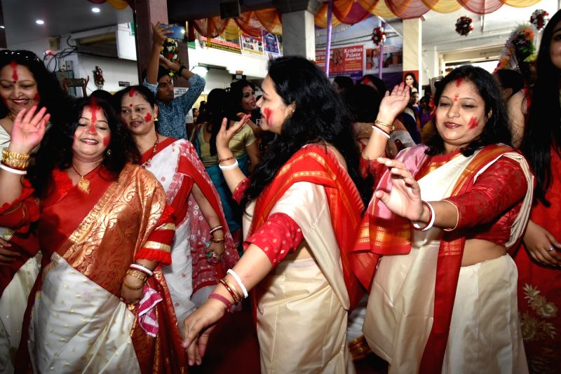 Woman participate in Sindoor Khela - a ritual in which married woman apply vermilion to goddess Durga and thereafter to each other on the last day of Durga Puja - in Ranchi on Sept 30, 2017.