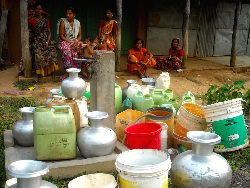 Women and children wait to collect drinking water from a supply water line in the Gandhigram village on the outskirts of Agartala on April 19,  2014.
