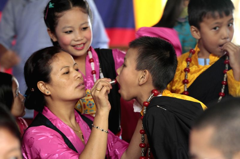 Women applies lipstick to a child ahead of a cultural performance during the 54th anniversary of Tibetan Democracy Day at Tsug la Khang temple in McLeod Ganj of Dharamshala on Sept 2, 2014.